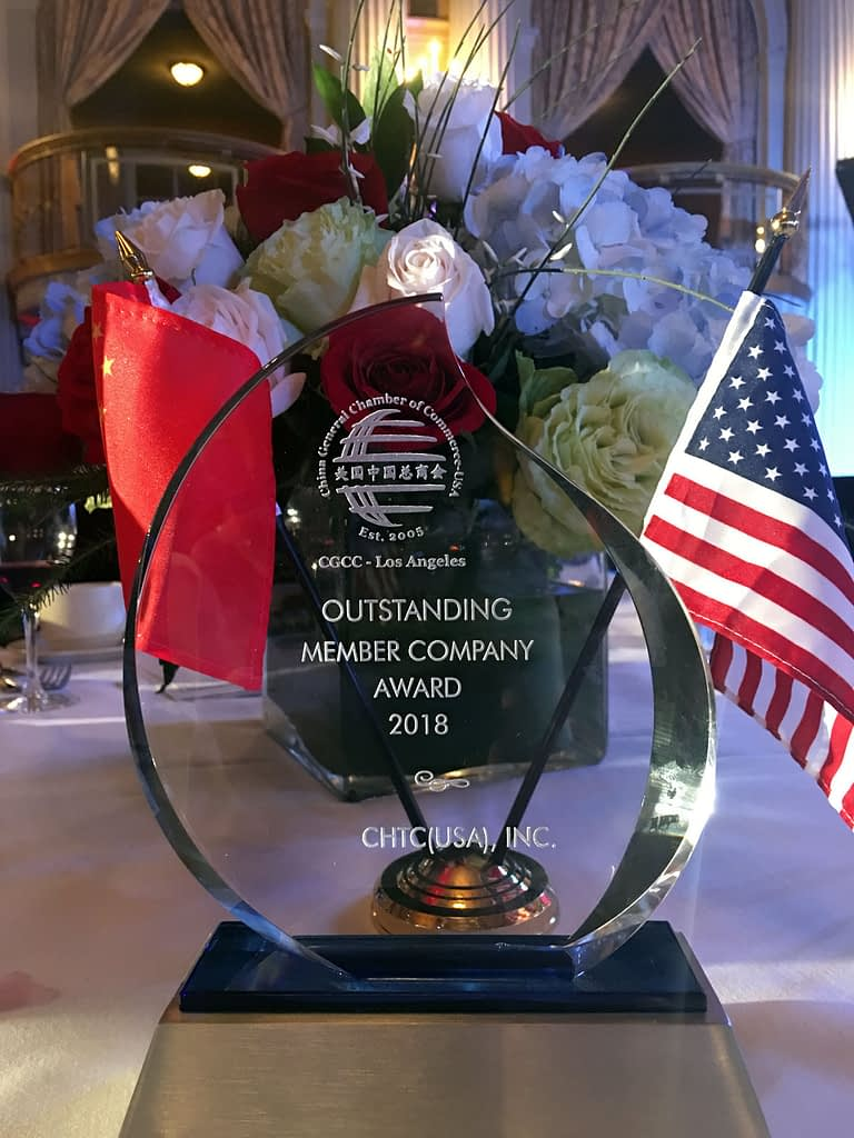 An award on a table in front of a floral centerpiece with American and Chinese flags